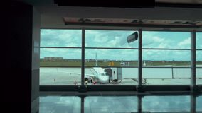 Establishing shot of a fully boarded airplane. As viewed through a gate window. 4K footage stock video footage
