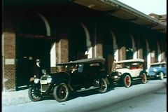 Establishing shot of railway station with vintage cars parked outside stock video footage