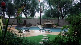 Establishing Shot of Residential Arizona Backyard Pool in a Monsoon. A daytime establishing shot of an Arizona residence backyard pool in a monsoon or rain storm stock video footage