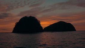 Passing a tropical island cluster at sunset. Establishing shot of a tropical island cluster at sunset. 4K UHD footage stock video footage