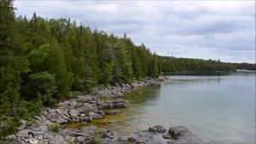 Establishing shot - Waves hitting the shore of the Huron Lake shore near Tobermory on Bruce Peninsula Ontario Canada. Waves hitting the shore of the Huron Lake stock video footage