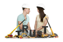 Establishing trust: Young couple with machines building trust-wo. Building up trust concept: Smiling young men and women along with construction machines Stock Photography