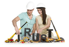 Establishing trust: Young smiling couple with machines building Royalty Free Stock Image