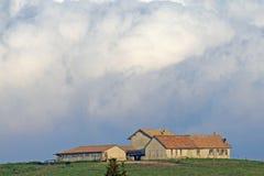 Establo sobre la colina con las nubes blancas enormes Foto de archivo