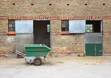 Establos vacíos del caballo con el carro de la suciedad en el asfalto Foto de archivo libre de regalías