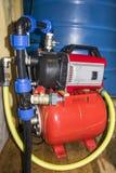 Estación de bombeo para el agua, conexiones de los tubos, mangueras, barril plástico con agua Abastecimiento de agua autónomo Imagen de archivo libre de regalías