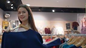 Estación de los descuentos, ropa que intenta sonriente de la mujer del comprador delante del espejo en tienda de moda durante ven almacen de video