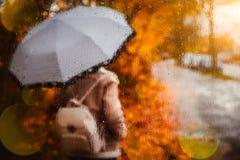 Estación de oro hermosa del otoño Acuarela como muchacha rubia borrosa con la mochila y soportes de paraguas brillantes debajo de imágenes de archivo libres de regalías