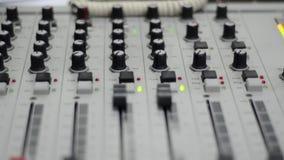 Estación de radio Consola, ordenador y micrófono de mezcla de varias trayectorias profesionales en la sala de control Registració almacen de video