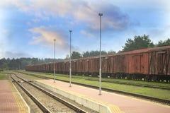 Estación de tren y carros rojos de la carga Imagen de archivo