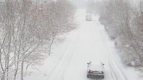 Estación del invierno El coche monta en un camino nevoso almacen de metraje de vídeo