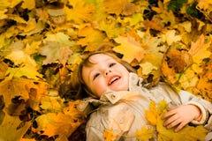 Estación del otoño - niño en hojas caidas Foto de archivo