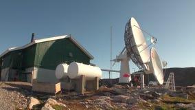 Estación y aereal parabólico en montañas en la orilla de Groenlandia en el Océano ártico almacen de video