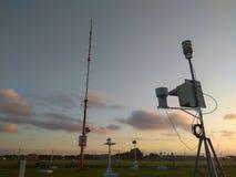 Estaci?n meteorol?gica autom?tica port?til en el aeropuerto de Ngurah Rai debajo de las nubes de altocumulus hermosas Esta herram fotografía de archivo libre de regalías