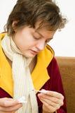 Estación del frío y de gripe, la mujer blanca está tomando temperatura Imagenes de archivo