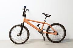 Estacionamento alaranjado da bicicleta do flatland no fundo do branco do escritório Imagem de Stock Royalty Free