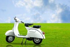 Estacionamento branco do motobike do vintage na grama Imagens de Stock Royalty Free