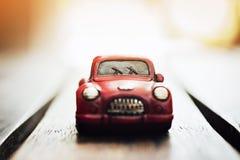Estacionamento clássico vermelho do carro do vintage no assoalho de madeira com alargamento da luz solar Imagens de Stock