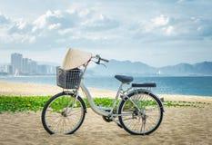 Estacionamento da bicicleta na areia da praia ao pendurar vietnamiana do chapéu dos guiador vietnam Imagens de Stock Royalty Free