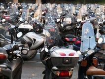 Estacionamento de 'trotinette's e de motocicletas numerosos na cidade italiana de Genoa fotografia de stock royalty free