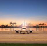 Estacionamento do avião de carga em pistas de decolagem do aeroporto e em porto de transporte atrás Fotografia de Stock