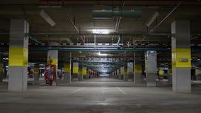 Estacionamento subterrâneo com luz de néon, extintor e tubulação, Fotos de Stock Royalty Free