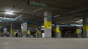 Estacionamento subterrâneo com luz de néon, extintor e tubulação, Imagem de Stock