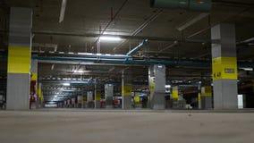 Estacionamento subterrâneo com luz de néon, extintor e tubulação, Imagens de Stock