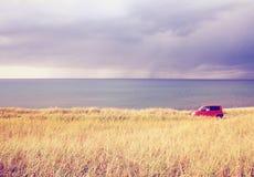 Estacionamento vermelho do carro no campo fotos de stock
