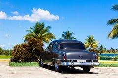 Estacionamiento americano del Oldtimer de Cuba debajo de las palmas Foto de archivo