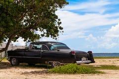 Estacionamiento americano del Oldtimer de Cuba en la playa Foto de archivo