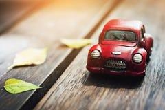 Estacionamiento clásico rojo del coche del vintage en el piso de madera con Autumn Sunlight imagen de archivo libre de regalías