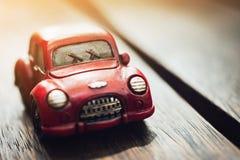 Estacionamiento clásico rojo del coche del vintage en el piso de madera con el fondo de la llamarada de la luz del sol Fotografía de archivo libre de regalías