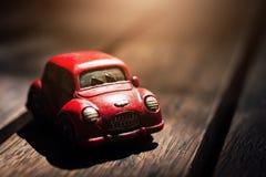 Estacionamiento clásico rojo del coche del vintage en el piso de madera con el fondo de la llamarada de la luz del sol Fotos de archivo
