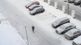 Estacionamiento con la nieve del invierno, resbaladiza, gente que camina, visión aérea metrajes