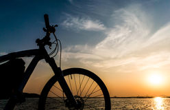 Estacionamiento de la bici de montaña en el mar y el fondo del cielo de la puesta del sol Fotografía de archivo