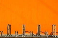Estacionamiento de la bicicleta y pared anaranjada Imágenes de archivo libres de regalías
