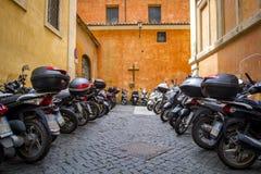Estacionamiento de la motocicleta al lado de la terraza de una iglesia Ventanas viejas hermosas en Roma (Italia) Foto de archivo