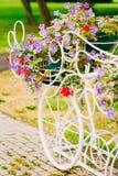 Estacionamiento decorativo blanco de la bicicleta en jardín Foto de archivo