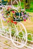 Estacionamiento decorativo blanco de la bicicleta en jardín Imágenes de archivo libres de regalías