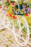Estacionamiento decorativo blanco de la bicicleta en jardín Fotos de archivo libres de regalías