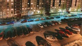 Estacionamiento del coche en el patio de las construcciones de viviendas en el vídeo del lapso de la noche Cambio inclinable Efec metrajes