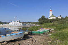 Estacionamiento en el río de Sukhona de la orilla cerca de la suposición de la iglesia de la Virgen bendecida en la ciudad de Tot foto de archivo libre de regalías