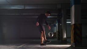 Estacionamiento subterráneo Hombre atlético del fútbol que entrena a sus habilidades del fútbol Cogiendo la bola en el suyo detrá almacen de metraje de vídeo