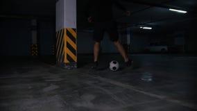 Estacionamiento subterráneo Hombre atlético del fútbol que entrena a sus habilidades del fútbol Llevar la bola alrededor del pila almacen de video