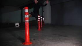 Estacionamiento subterráneo Hombre atlético del fútbol que entrena a sus habilidades del fútbol Llevar los obstáculos que bordean almacen de video
