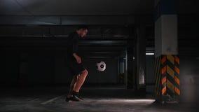 Estacionamiento subterráneo Hombre atlético del fútbol que entrena a sus habilidades del fútbol Retroceso de la bola con el pie d almacen de metraje de vídeo