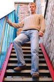 A estada à moda nova do homem em escadas aproxima a parede de tijolo. Imagem de Stock Royalty Free