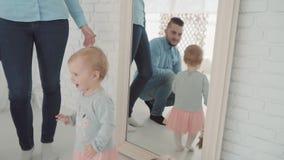 Estada bonita da menina perto do espelho com seus família e cão Movimento lento Marco miliário do bebê, criança, bebê de um ano vídeos de arquivo