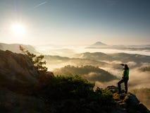 Estada da silhueta do homem no pico afiado da rocha Satisfaça o caminhante apreciam a vista foto de stock royalty free
